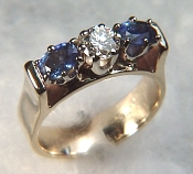 Diamond and sapphire ring with bridged mounting
